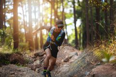 A man Runner of Trail . and athlete`s feet wearing sports shoes for trail running in the forest royalty free stock image