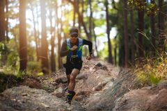 A man Runner of Trail . and athlete`s feet wearing sports shoes for trail running in the forest royalty free stock photos