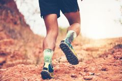 A man Runner of Trail . and Close up of an athlete`s feet wearing sports shoes for trail running in the mountains stock photos