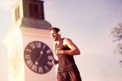 Man runner training doing outdoor. Running man runner training doing outdoor city run sprinting along the famous Clock Petrovaradin fortress, urban healthy Stock Photo