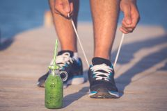 Man runner tying laces before training. Green smoothie fitness man lacing running shoes. Athlete runner with green vegetable detox juice getting ready for royalty free stock photography