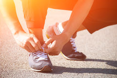 Man runner tying shoelaces. Close up man runner tying shoelaces Royalty Free Stock Photography