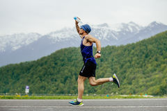 Man runner on water point pours face from water bottle Stock Photography