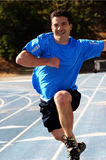 Man running. On a blue racetrack Royalty Free Stock Photography