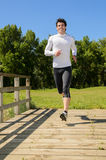 Man Running. Handsome man running in a park with headphones Royalty Free Stock Images