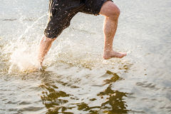 A man running along a beach and splashing water.  Royalty Free Stock Images