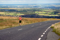 Man running along a country lane. A man running along a countryside road Stock Images