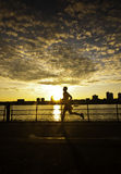 Man running along river at sunset Stock Images