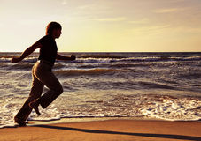 Man running along seashore Stock Photos