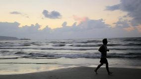 Man running along seashore stock video