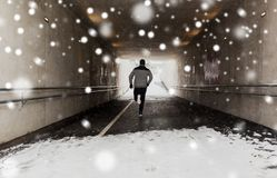 Man running along subway tunnel in winter. Fitness, sport, people, season and healthy lifestyle concept - young man running along pedestrian subway tunnel in Royalty Free Stock Photography
