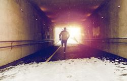 Man running along subway tunnel in winter. Fitness, sport, people, season and healthy lifestyle concept - young man running along pedestrian subway tunnel in Royalty Free Stock Photo