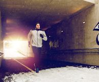 Man running along subway tunnel in winter. Fitness, sport, people, season and healthy lifestyle concept - young man running along pedestrian subway tunnel in Stock Photography