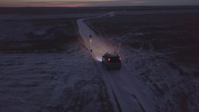 Man running along winter road with dog and car moving behind them. In night landscape. Car driving along rural winter road behind man jogging with dog aerial stock image