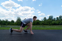 The man is running around the stadium. Training outdoors. From the side view royalty free stock photo