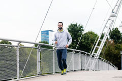 Man running as sport in the city over bridge Stock Photography