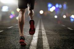 Man running on asphalt road. At night royalty free stock image