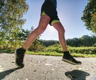 Man running on asphalt track. Athlete running fast in a park. With dense trees in the background royalty free stock image