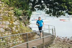 Man running. Attractive man running on a wooden walkway over the sea. Daily training Royalty Free Stock Photo