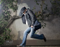 Man running away along the wall Stock Photo