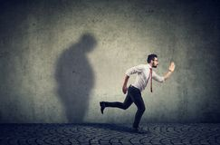 Man running away from his sad gloomy fat shadow on the wall. Mental health and body weight control concept royalty free stock photos