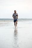 Man running barefoot on beach by water Stock Photos