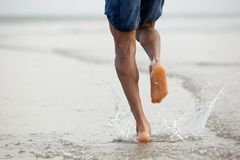 Man running barefoot in water. Rear view low angle view of a man running barefoot in water Stock Image