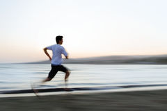 Man Running on Beach. Man jogging on the beach with motion blur Royalty Free Stock Images