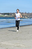 Man running on the beach Stock Images