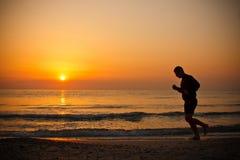 Man running on the beach stock photography