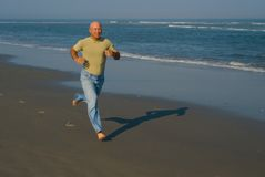 Man Running on the beach. Man (bab-boomer) running on the beach on a summer day Royalty Free Stock Photography