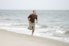 Man running on beach Stock Images