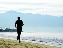 Man running on the beach. In the morning Stock Image