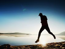 Man running on beach against backdrop of a beautiful sunset. Sand of mountain lake Stock Images