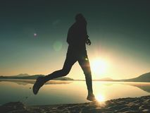 Man running on beach against backdrop of a beautiful sunset. Sand of mountain lake Royalty Free Stock Photos