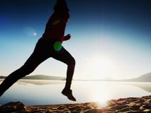 Man running on beach against backdrop of a beautiful sunset. Sand of mountain lake Royalty Free Stock Photo