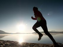 Man running on beach against backdrop of a beautiful sunset. Sand of mountain lake. Man running on the beach against the backdrop of a beautiful sunset. Sand of Stock Images
