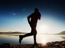 Man running on beach against backdrop of a beautiful sunset. Sand of mountain lake. Man running on the beach against the backdrop of a beautiful sunset. Sand of Stock Image