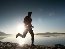 Man running on beach against backdrop of a beautiful sunset. Sand of mountain lake Stock Photo