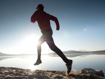 Man running on beach against backdrop of a beautiful sunset. Sand of mountain lake Royalty Free Stock Photography