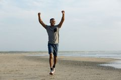 Man running on beach with arms outstretched Stock Photo