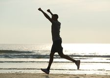 Man running on beach with arms raised Stock Photo