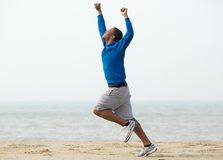 Man running at the beach with arms raised in victory. Young black man running at the beach with arms raised in victory Royalty Free Stock Photo