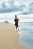Man Running On Beach, Jogging During Outdoor Workout. Sports Con Royalty Free Stock Photos