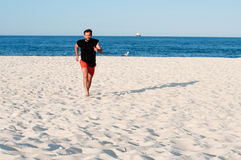 Man is running on the beach. Man doing exercise on seashore. Royalty Free Stock Photography