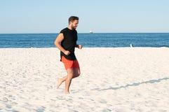 Man is running on the beach. Man doing exercise on seashore. Stock Photo