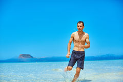 Man running on the beach Stock Photos