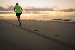 Man is running by the beach. At sunrise stock photos