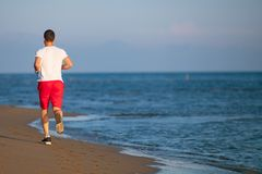 Man running on the beach at sunset. Young Man running on the beach at sunset Royalty Free Stock Images