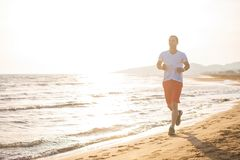 Man running on the beach at sunset. Young Man running on the beach at sunset Stock Photography